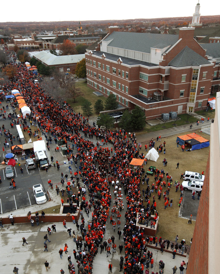 Photo - The OSU team makes their way to the stadium during the Spirit Walk before the Bedlam college football game between the Oklahoma State University Cowboys (OSU) and the University of Oklahoma Sooners (OU) at Boone Pickens Stadium in Stillwater, Okla., Saturday, Dec. 3, 2011. Photo by Bryan Terry, The Oklahoman