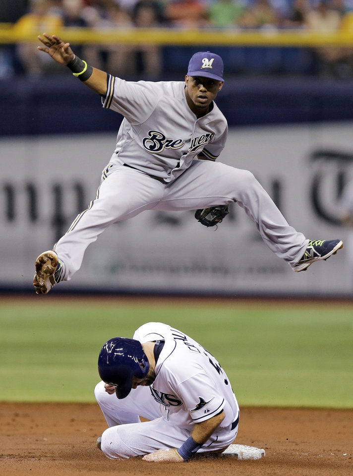 Photo - Milwaukee Brewers shortstop Jean Segura leaps over Tampa Bay Rays' Curt Casali after forcing him at second base on a fielder's choice by Kevin Kiermaier during the third inning of a baseball game Tuesday, July 29, 2014, in St. Petersburg, Fla. (AP Photo/Chris O'Meara)