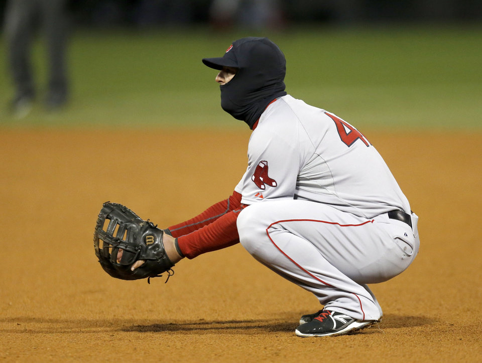 Photo - Wearing a balaclava, Boston Red Sox first baseman Mike Napoli takes a defensive stance during the sixth inning of a baseball game against the Chicago White Sox on Tuesday, April 15, 2014, in Chicago. Temperatures were in the mid-30s for the game. (AP Photo/Charles Rex Arbogast)