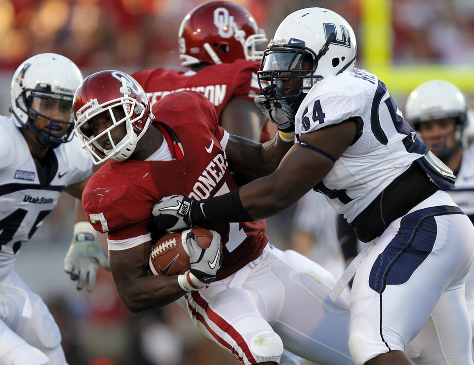 Photo - Oklahoma's DeMarco Murray (7) is brought down by Utah State's Nathan Royster (54) during the first half of the college football game between the University of Oklahoma Sooners (OU) and Utah State University Aggies (USU) at the Gaylord Family-Oklahoma Memorial Stadium on Saturday, Sept. 4, 2010, in Norman, Okla.   Photo by Chris Landsberger, The Oklahoman