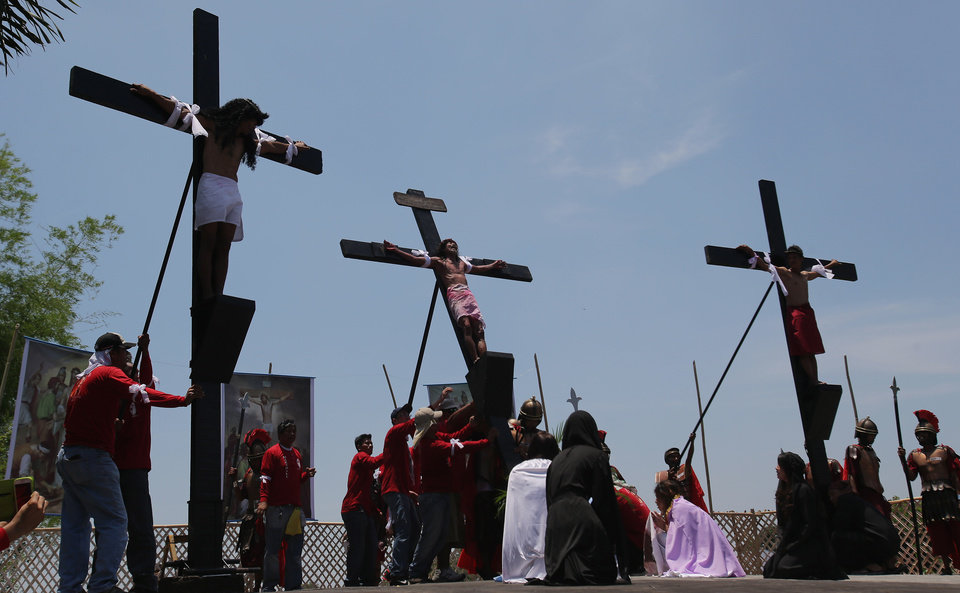 Photo - A Filipino devotee who was nailed to a cross is lifted as they try to re-enact the crucifixion of Jesus Christ in San Juan village, Pampanga province, northern Philippines on Friday, April 18, 2014. Church leaders and health officials have spoken against the practice which mixes Roman Catholic devotion with folk belief, but the annual rites continue to draw participants and huge crowds. (AP Photo/Aaron Favila)