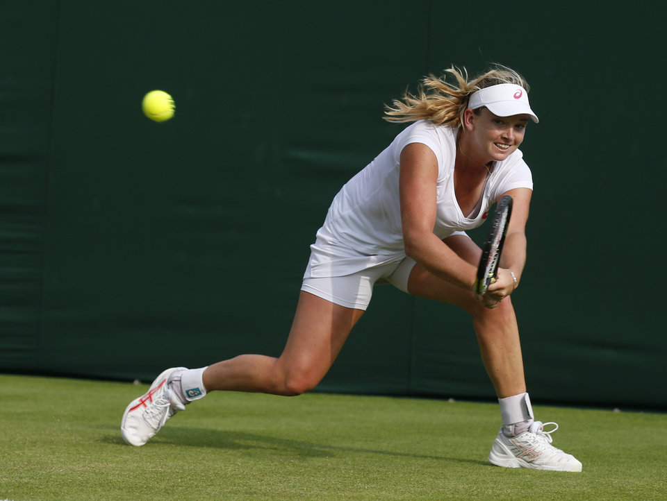 Photo - Coco Vandeweghe of the U.S. plays a return to Garbine Muguruza of Spain during their first round match at the All England Lawn Tennis Championships in Wimbledon, London,  Monday, June  23, 2014. (AP Photo/Sang Tan)
