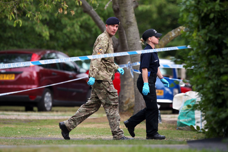 Photo -   A member of the Royal Logistic Corps bomb disposal team walks with a police officer close to the home of Saad al-Hilli, in Claygate, England, who was shot dead with three others while vacationing in the French Alps, Monday Sept. 10, 2012. UK police say they have evacuated homes near the house of a British-Iraqi couple slain while vacationing in the French Alps because of concerns about items found at the property. (AP Photo/PA, Steve Parsons) UNITED KINGDOM OUT NO SALES NO ARCHIVE