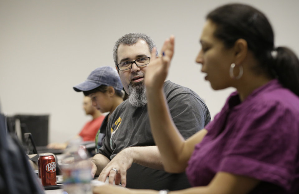 Photo - In this Thursday, July 18, 2013, photo, Kyle Maxwell, center, left, talks with Michelle Klinger, right, during a monthly
