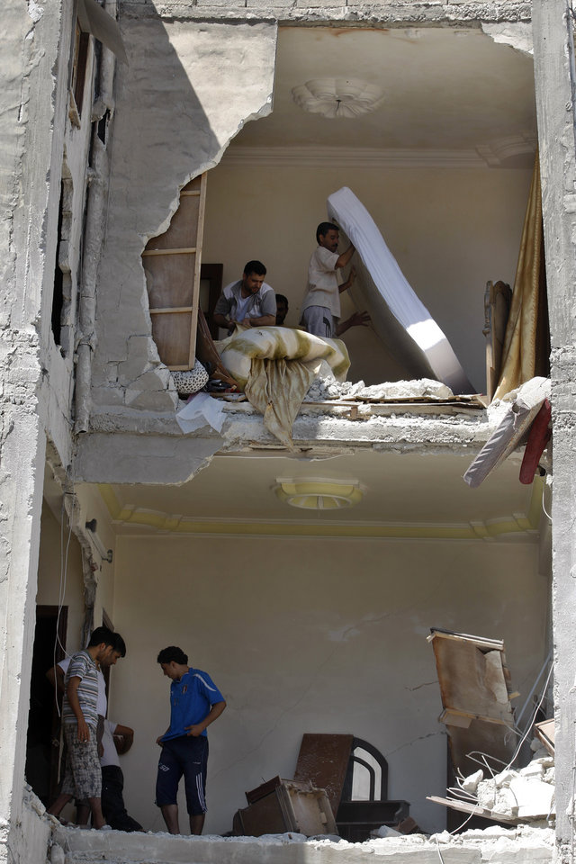 Photo -   Syrians salvage what they can of their belongings from a building that was hit during a Syrian government airstrike in Aleppo, Syria, Sunday, Aug. 19, 2012 (AP Photo/ Khalil Hamra)