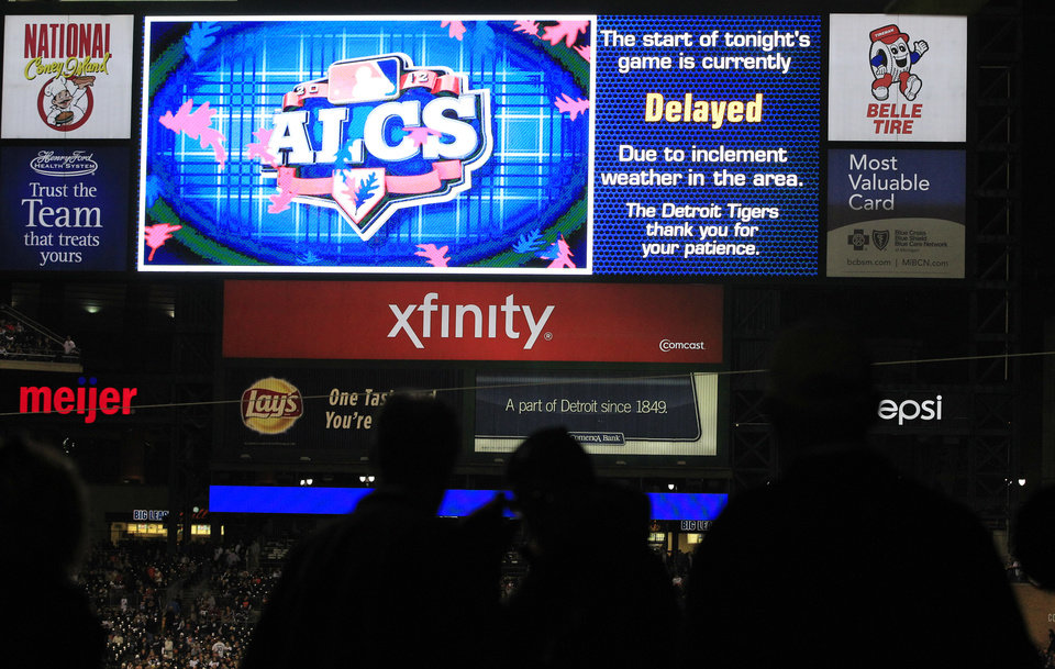 Photo -   Fans wait as Game 4 of the American League championship series between the Detroit Tigers and New York Yankees is delayed due to weather Wednesday, Oct. 17, 2012, in Detroit. (AP Photo/Carlos Osorio)