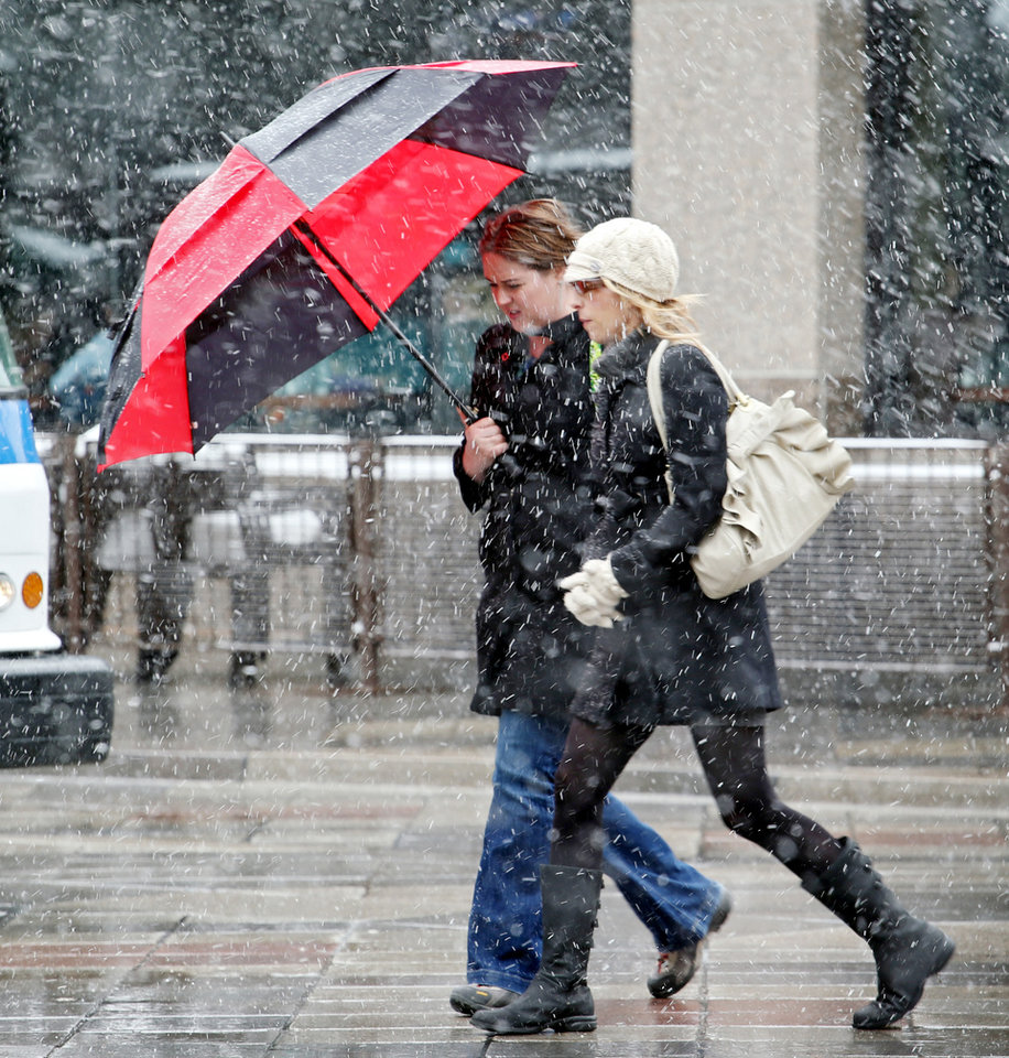 Photo - Two women share an umbrella to ward off snow as they walk the 16th Street Mall during the noon hour in Denver on Wednesday, April 17, 2013. As much as five inches of new snow is forecast for Denver. (AP Photo/Ed Andrieski)