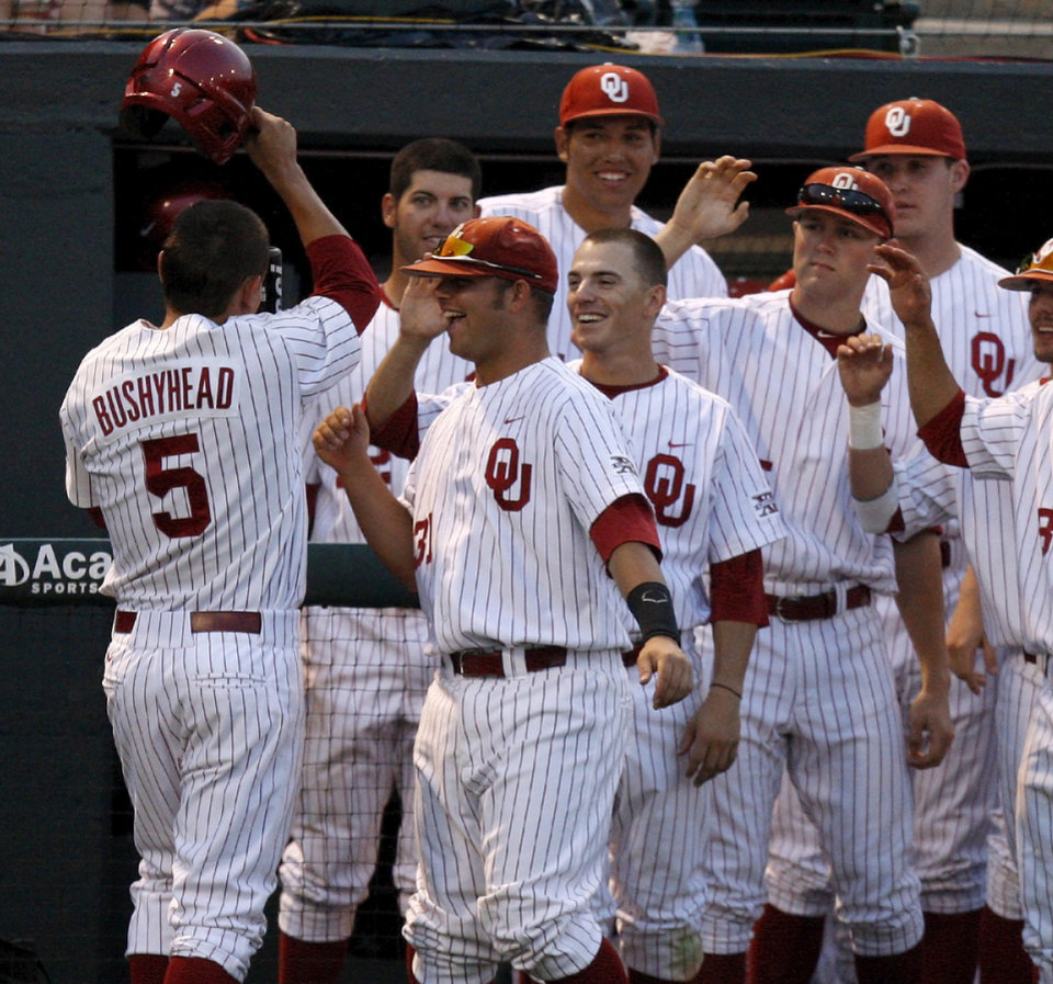 Photo - Oklahoma's Caleb Bushyhead celebrates withTanner Toal (31) and others after scoring in the fifth inning of their baseball game against Arkansas at L. Dale Mitchell Park in Norman, Okla., Tuesday, April 10, 2012. Photo by Bryan Terry, The Oklahoman