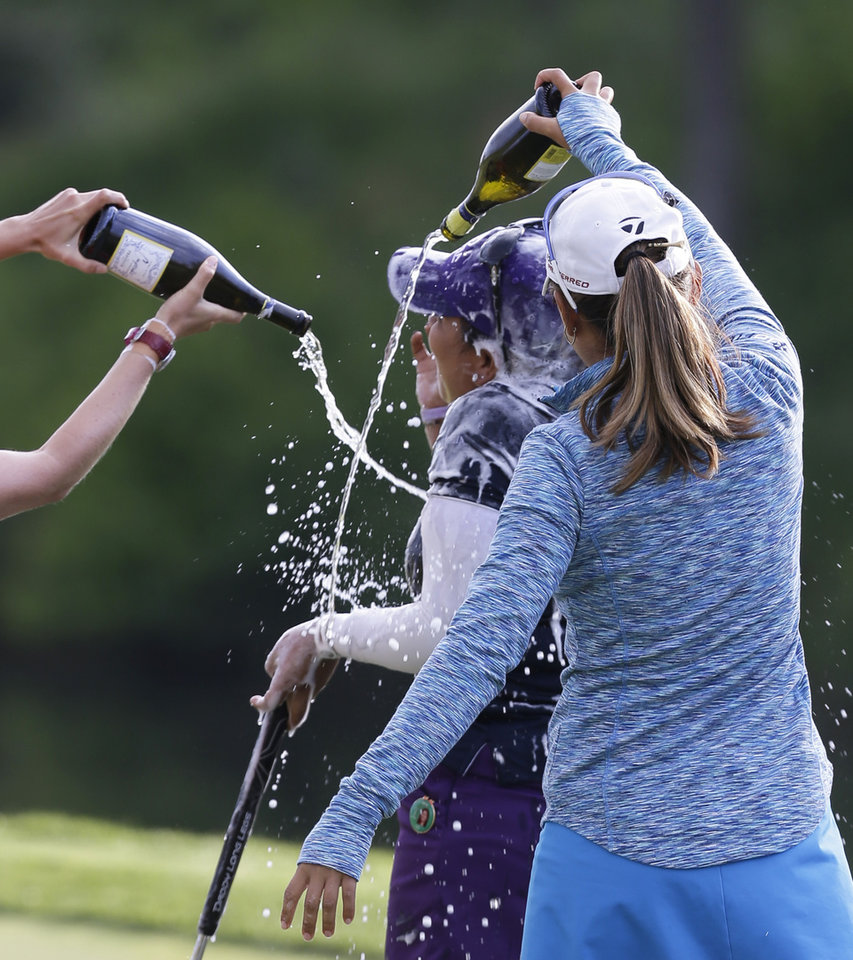 Photo - Lizette Salas is doused by fellow golfer Nina Hrigae, right, as she celebrates winning the Kingsmill Championship golf tournament at the Kingsmill resort  in Williamsburg, Va., Sunday, May 18, 2014.  Salas won her first LPGA event after shooting an even par-71 leaving her at 13-under for the tournament.  (AP Photo/Steve Helber)