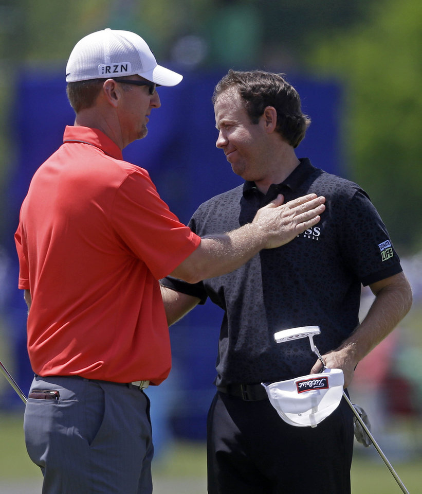 Photo - Erik Compton, right, is congratulated by David Duval after the two finished the day on the ninth green during the opening round of the Zurich Classic golf tournament at TPC Louisiana in Avondale, La., Thursday, April 24, 2014. Compton finished six under par and Duval finished 4 under. (AP Photo/Gerald Herbert)