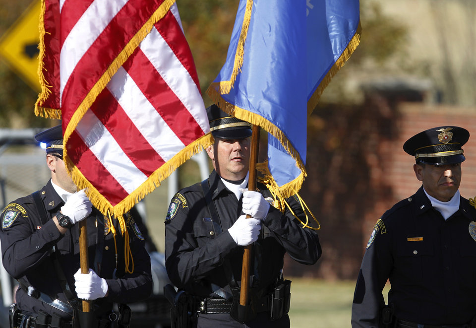 The MWC Police Department Honor Guard carries the American and the state flags during the parade. The city of Midwest City teamed with civic leaders and local merchants to display their appreciation for veterans and active military forces by staging a hour-long Veteran\'s Day parade that stretched more than a mile and a half along three of the city\'s busiest streets Monday morning, Nov. 12, 2012. Hundreds of people lined the parade route, many of them waving small American flags that had ben distributed by volunteers who marched near the front of the parade. A fly-over performed by F-16s from the138th Fighter Wing, Oklahoma Air National Guard unit in Tulsa thrilled spectators. Five veterans representing military personnel who served in five wars and military actions served as Grand Marshals for the parade. Leading the parade was the Naval Reserve seven-story American flag, carried by 100 volunteers from First National Bank of Midwest City, Advantage Bank and the Tinker Federal Credit Union. The flag is 50 feet by 76 feet, weighs 110 pounds and was sponsored by the MWC Chapter of Disabled American Veterans. Photo by Jim Beckel, The Oklahoman