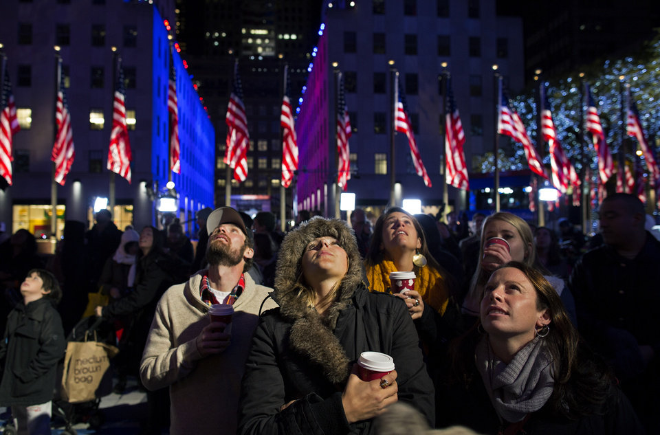 Photo -   People watch election results displayed on a utility lift suspended from the front of the GE Building at Rockefeller Center, in New York, Tuesday, Nov. 6, 2012. From center left are Bryan Fletcher of Park City, Utah; Jen Hudak, Salt Lake City; Lindsay Arnold, Park City; K.C. Oakley, Park City, and Emily Cook, Park City. After a year of campaigning, polls have begun to close after Americans across the United States headed to the polls to decide the winner of the tight presidential race between President Barack Obama and Republican presidential candidate, former Massachusetts Gov. Mitt Romney. (AP Photo/Craig Ruttle)
