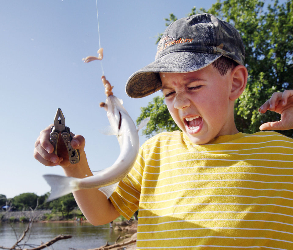 Seven-year-old Isaac Mardirosian jumps back as the sand bass that he caught flops out of his hand during the Kid's Fishing Derby at Arcadia Lake in Edmond, OK, Saturday, June 4, 2011. By Paul Hellstern, The Oklahoman