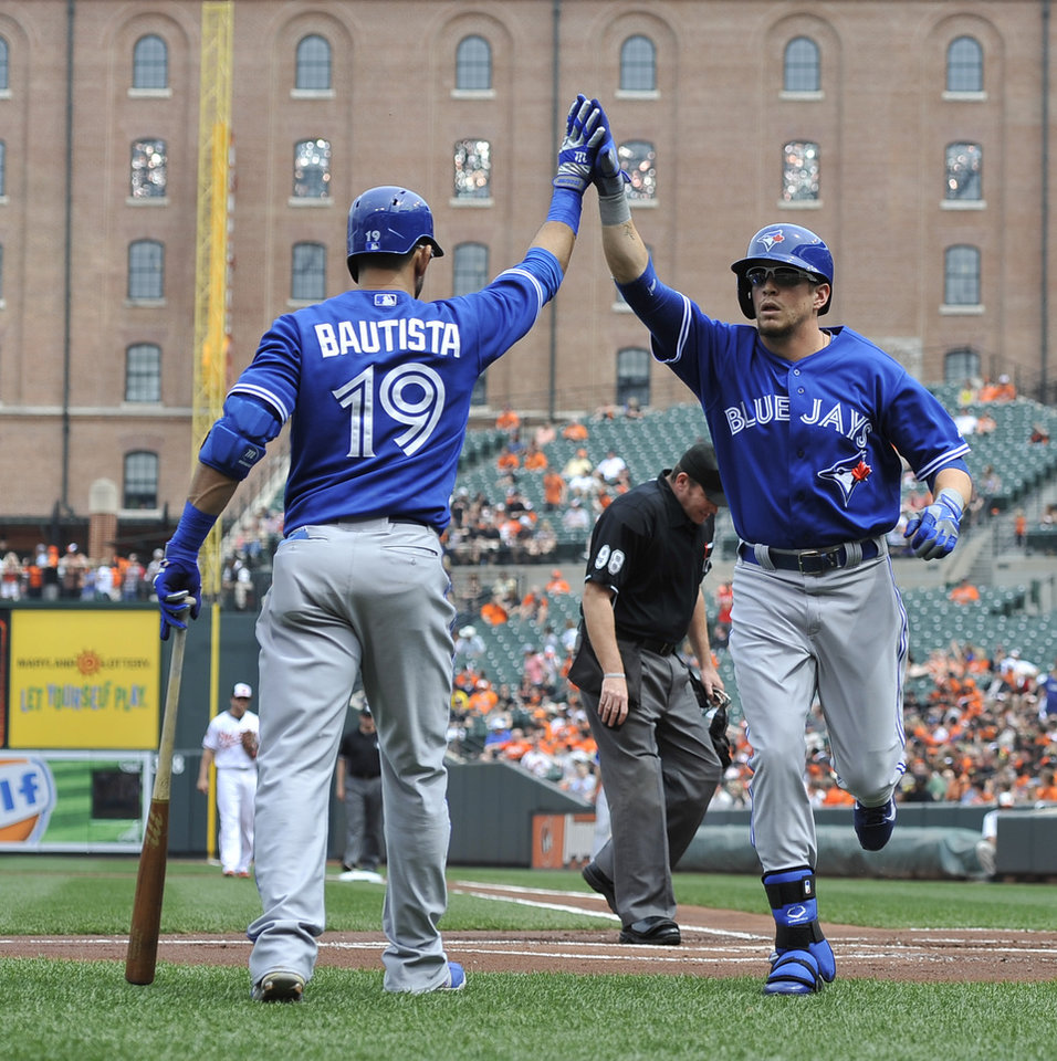 Photo - Toronto Blue Jays Colby Rasmus, right, is congratulated by teammate Jose Bautista after hitting a solo home run against the Baltimore Orioles in the first inning of a baseball game on Sunday, April 13, 2014, in Baltimore. (AP Photo/Gail Burton)