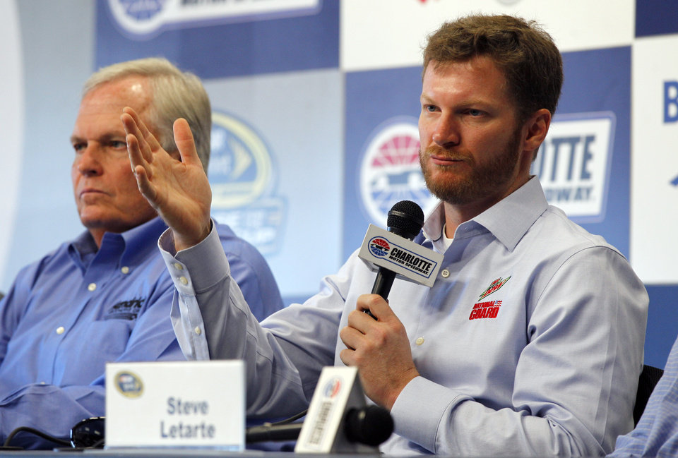 Photo -   Dale Earnhardt Jr, right, talks about missing the next two races with his second concussion in the past six weeks during a news conference prior to practice for Saturday's NASCAR Bank of America 500 NASCAR Sprint Cup series auto race in Concord, N.C., Thursday, Oct. 11, 2012. Team owner Rick Hendrick, left, looks on. (AP Photo/Chuck Burton)