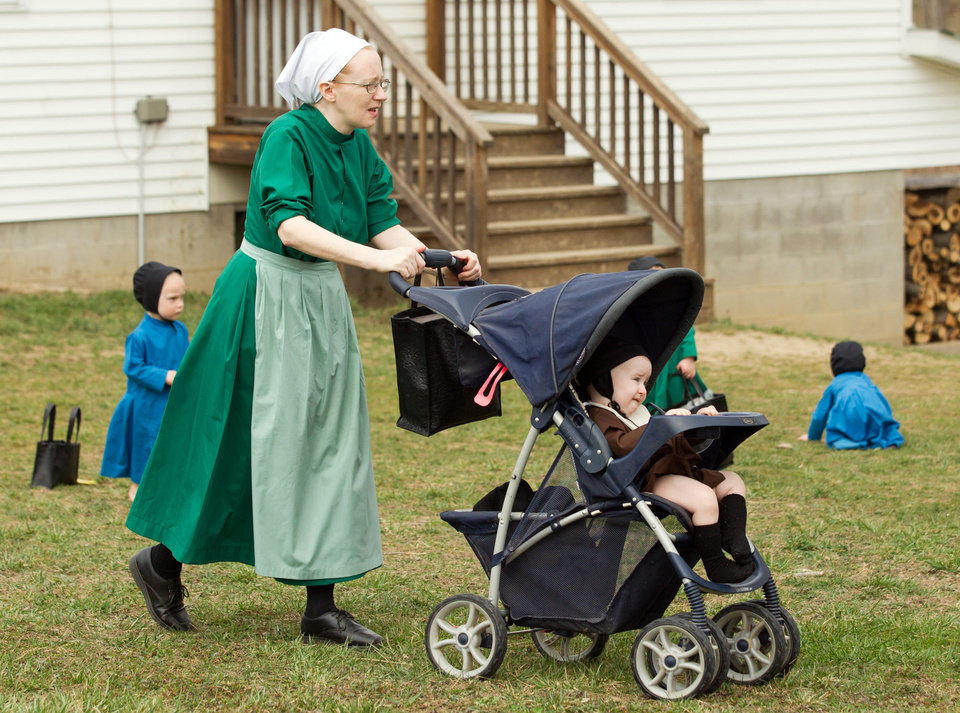 Photo - Emma Miller pushes her son in a stroller outside the schoolhouse in Bergholz, Ohio, Tuesday, April 9, 2013. Miller, along with three other women and a man from this tight-knit community in rural eastern Ohio, will enter prison on Friday, April 12, joining nine already behind bars on hate crimes convictions for hair- and beard-cutting attacks against fellow Amish. (AP Photo/Scott R. Galvin)
