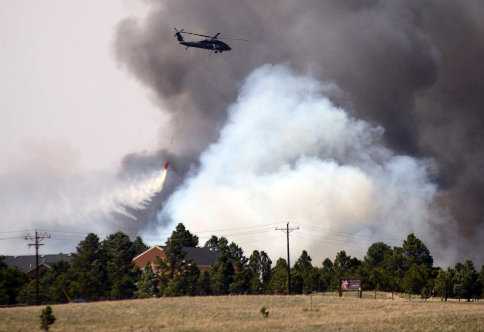 Photo - A helicopter from Ft. Carson's 4th Combat Aviation Brigade drops water behind a home and between advancing flames as the Black Forest Fire burns out of control for a second straight day near Colorado Springs, Colo. on Wednesday, June 12, 2013. Three Colorado wildfires fueled by hot temperatures, gusty winds and thick, bone-dry forests have together burned dozens of homes and led to the evacuation of more than 7,000 residents and nearly 1,000 inmates at medium-security prison. (AP Photo/Bryan Oller)