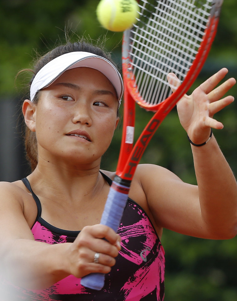 Photo - Grace Min of the U.S, returns the ball to Spain's Garbine Muguruza during the first round match of  the French Open tennis tournament at the Roland Garros stadium, in Paris, France, Sunday, May 25, 2014. (AP Photo/Michel Euler)