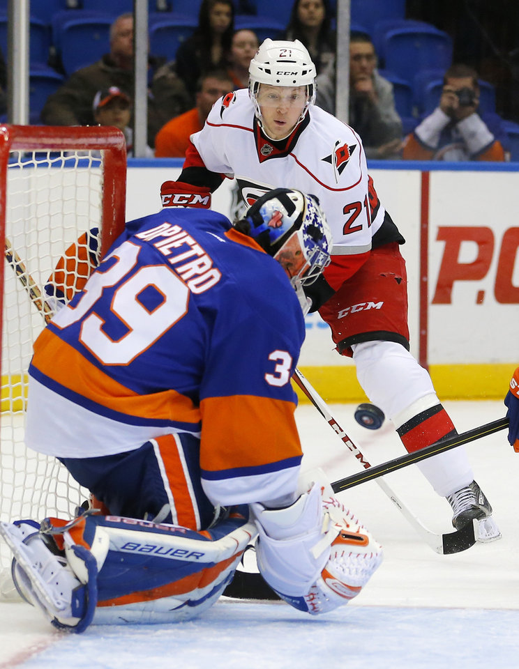 Carolina Hurricanes left wing Drayson Bowman (21) watches New York Islanders goalie Rick DiPietro (39) stop his shot during the first period of an NHL hockey game at the Nassau Coliseum in Uniondale, N.Y., Monday, Feb.11, 2013. (AP Photo/Paul J. Bereswill)