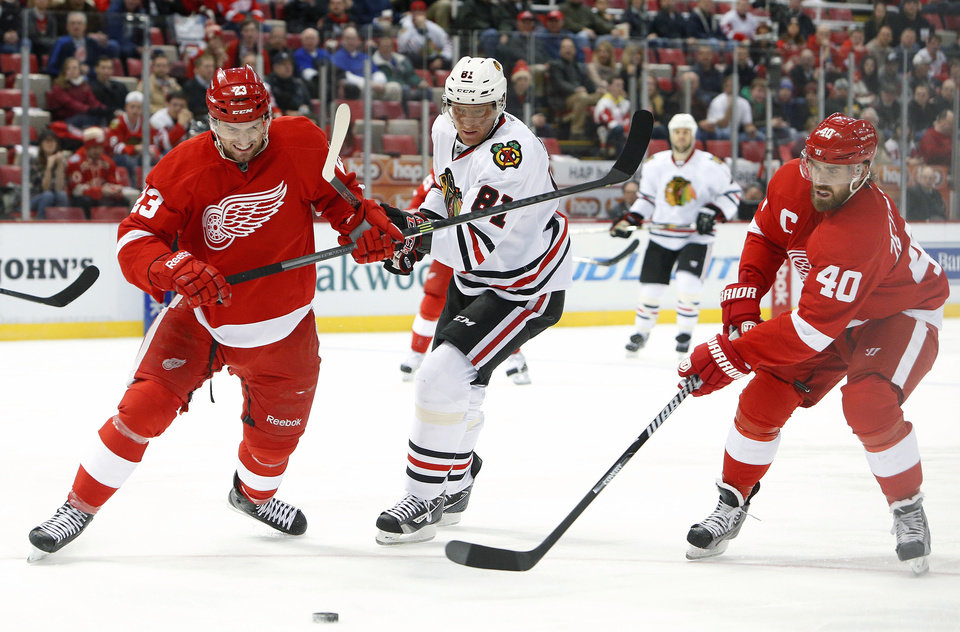 Photo - Detroit Red Wings defenseman Brian Lashoff (23) battles with Chicago Blackhawks right wing Marian Hossa (81), of the Czech Republic, and Henrik Zetterberg (40), of Sweden, in the first period of an NHL hockey game Wednesday, Jan. 22, 2014, in Detroit. (AP Photo/Paul Sancya)