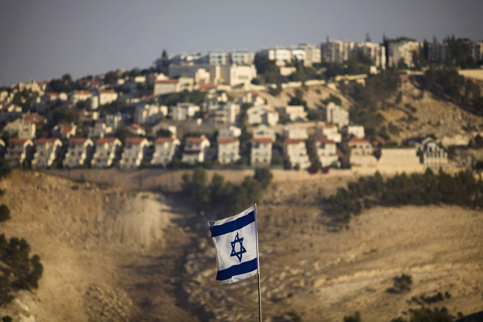 Photo - FILE - In this Monday, Sept. 7, 2009 file photo, an Israeli flag is seen in front of the West Bank Jewish settlement of Maaleh Adumim on the outskirts of Jerusalem. Israel on Wednesday, Oct. 30, 2013, announced plans to build 1,500 new homes in east Jerusalem, the part of the city claimed by the Palestinians, just hours after it freed a group of Palestinian prisoners as part of a deal to set peace talks in motion. (AP Photo/Bernat Armangue, File)