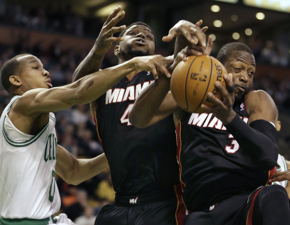 Boston Celtics guard Avery Bradley (0), left, grapples for control of the ball with Miami Heat forward Udonis Haslem (40), center, and Heat guard Dwyane Wade (3), right, in the first quarter of an NBA basketball game at the TD Garden in Boston, Sunday, Jan. 27, 2013. The Celtics beat the Heat 100-98. (AP Photo/Steven Senne)