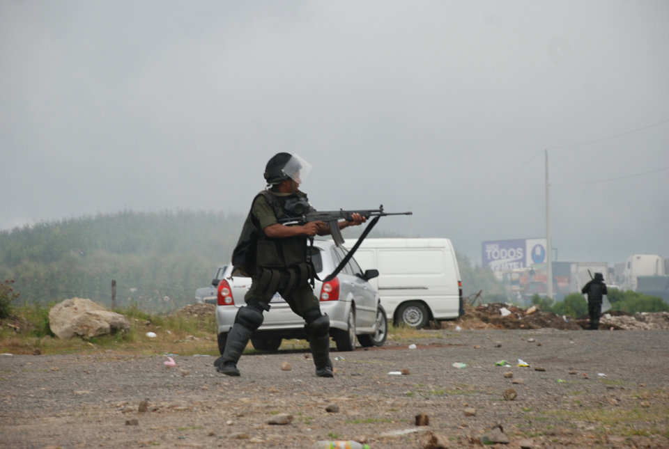 Military police dressed in riot gear react during clashes with peasants protesting against the cost of electricity in Santa Catarina Ixtahuacan, west of Guatemala City on Thursday Oct. 4, 2012. At least two people have been killed and dozen others seriously wounded in the confrontation between protesters and security forces. (AP Photo)