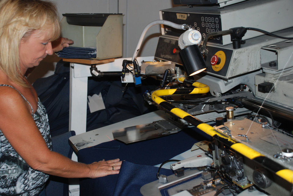 Round House employee Terri Landrum operates an automatic back pocket-setting machine for jeans.