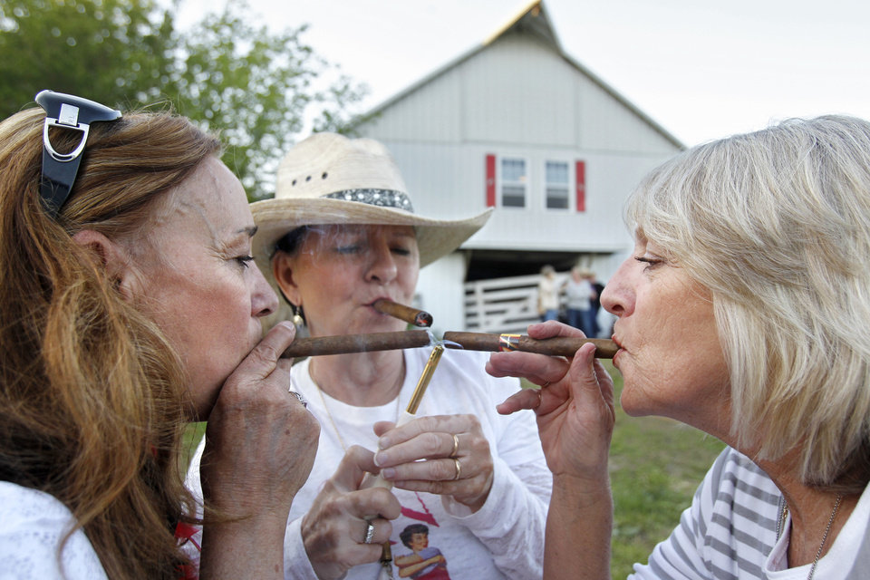 Photo - Members of Sisters on the Fly, Elaine Toland, from left, of Tecumseh, Kan., Deb Gaskill of Warsaw, Mo., and Lori Thompson of Leawood, Kan., light up cigars before dinner in Louisburg. Kansas, on April 21, 2012. Sisters on the Fly is a national group of camping enthusiasts founded by two actual sisters who love fly-fishing in Montana. (Jill Toyoshiba/Kansas City Star/MCT)