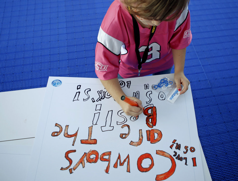 Photo - Alexandria Grill, 8, of Stillwater makes a sign before the OSU-Arizona game in Stillwater on Thursday. PHOTO BY BRYAN TERRY, The Oklahoman