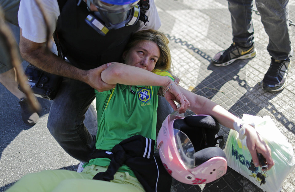 Photo - A press photographer helps a Brazil soccer fan affected by tear gas when she got caught up in clashes between police and protesters while trying to reach the stadium for the opening World Cup soccer game in Sao Paulo, Brazil, Thursday, June 12, 2014.  Brazilian police clashed with anti-World Cup protesters trying to block part of the main highway leading to the stadium that was hosting the opening match between Brazil and Croatia. (AP Photo/Nelson Antoine)