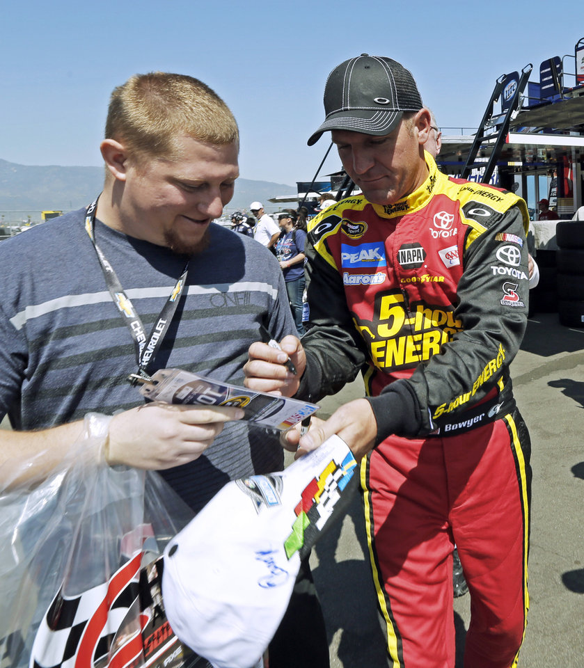 Clint Bowyer gives an autograph after practice for the NASCAR Sprint Cup series auto race in Fontana, Calif., Friday, March 22, 2013. (AP Photo/Reed Saxon)