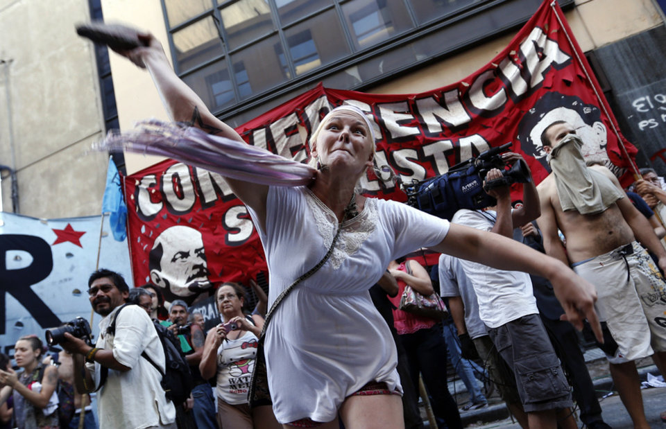 """A protester hurls a stone at police officers during a protest against the acquittal of 13 people accused in the disappearance of a young woman in Buenos Aires, Argentina, Wednesday, Dec. 12, 2012. The acquittal on Tuesday of 13 people accused in the disappearance of Marita Veron, a young woman who was allegedly kidnapped and forced into prostitution for """"VIP clients,"""" spread shock and outrage across Argentina on Wednesday, prompting street protests and calls by political leaders to impeach the three judges who delivered the verdict. (AP Photo/Victor R. Caivano)"""