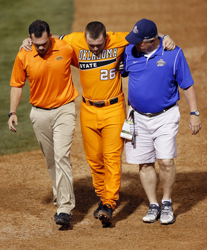 Photo - OSU's Zach Fish (26) is helped off of the fired after being injured during a Bedlam college baseball game between Oklahoma and Oklahoma State in the Big 12 baseball tournament at the Chickasaw Bricktown Ballpark in Oklahoma City,  Friday, May 23, 2014. Photo by Nate Billings, The Oklahoman