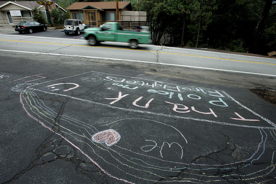 Photo - Residents of Pine Cove, Calif., thank firefighters and police in a chalk message along Highway 243. The evacuation order was rescinded in the areas affected by the Mountain Fire on Sunday, July 21, 2013. Thousands of people were allowed to return to their homes in Southern California mountain communities near Palm Springs on Sunday, after firefighters aided by heavy rain made substantial progress against a week-old wildfire that has burned across 42 square miles and destroyed seven homes.  (AP Photo/The Press-Enterprise, Terry Pierson)