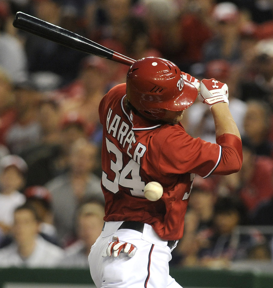 Photo -   Washington Nationals' batter Bryce Harper is hit by the pitch thrown by Philadelphia Phillies pitcher Cole Hamels during the first inning of their baseball game at Nationals Park, Sunday, May 6, 2012, in Washington. Harper later scored by stealing home from third base. (AP Photo/Richard Lipski)