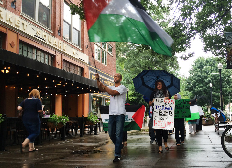 Photo - Ahmad Abuleil waves a Palestinian flag as he leads Amira Sakalla, head of University of Tennessee Students for Justice In Palestine, and others in a march in Knoxville, Tenn. on Friday, July 18, 2014. About 30 people gathered to show their support for Palestinians as fighting in the Gaza Strip continued. (AP Photo/Knoxville News Sentinel, Megan Boehnke)