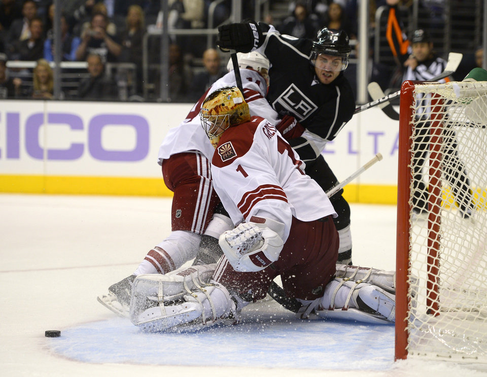 Photo - Los Angeles Kings center Mike Richards, right, tries to get a shot in on Phoenix Coyotes goalie Thomas Greiss, below, of Germany, as center Jeff Halpern helps defend during the second period of their NHL hockey game, Thursday, Oct. 24, 2013, in Los Angeles. (AP Photo/Mark J. Terrill)