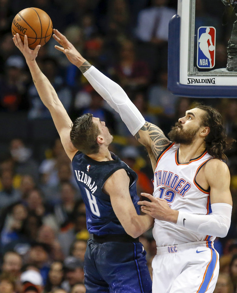 Photo - Oklahoma City's Steven Adams (12) blocks a shot by Orlando's Mario Hezonja (8) during an NBA basketball game between the Oklahoma City Thunder and the Orlando Magic at Chesapeake Energy Arena in Oklahoma City, Monday, Feb. 26, 2018. Photo by Nate Billings, The Oklahoman