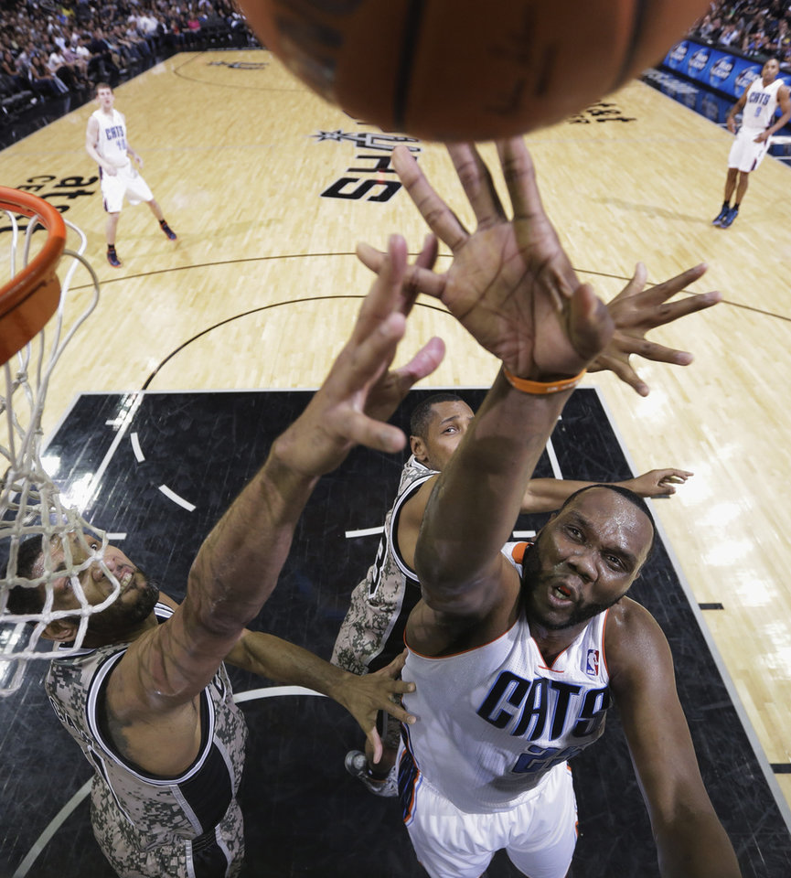 Photo - Charlotte Bobcats' Al Jefferson (25) shoots over San Antonio Spurs' Tim Duncan, left, during the first half of an NBA basketball game, Friday, Feb. 28, 2014, in San Antonio. (AP Photo/Eric Gay)