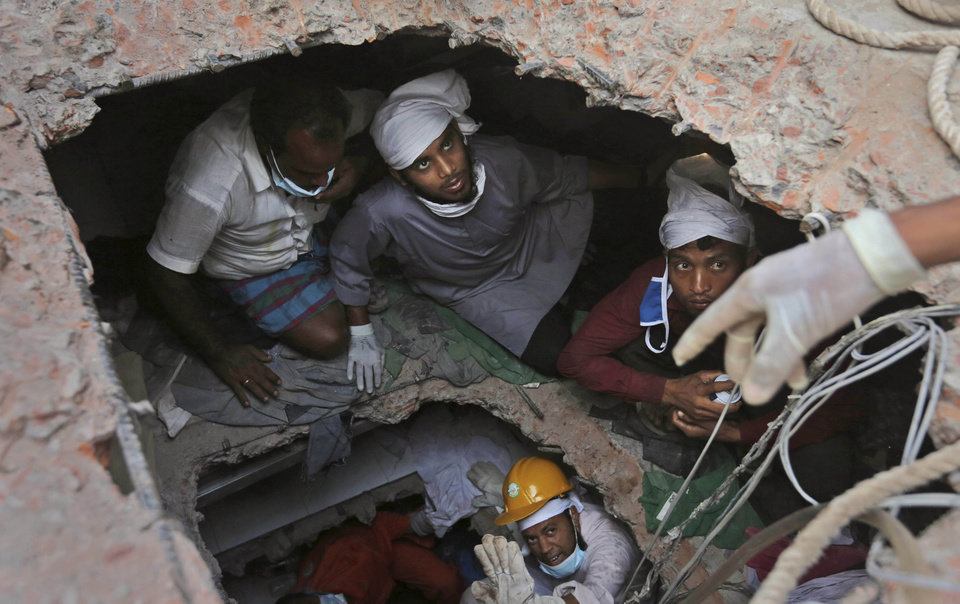 Photo - Bangladeshi rescue workers search for survivors as they are seen through a hole in the roof a building that collapsed Wednesday in Savar, near Dhaka, Bangladesh, Sunday, April 28, 2013. Bangladesh rescuers on Sunday located nine people alive inside the rubble of the multi-story building, as authorities announced they will now use heavy equipment to drill a central hole from the top to look for survivors and dead bodies. (AP Photo/Kevin Frayer)