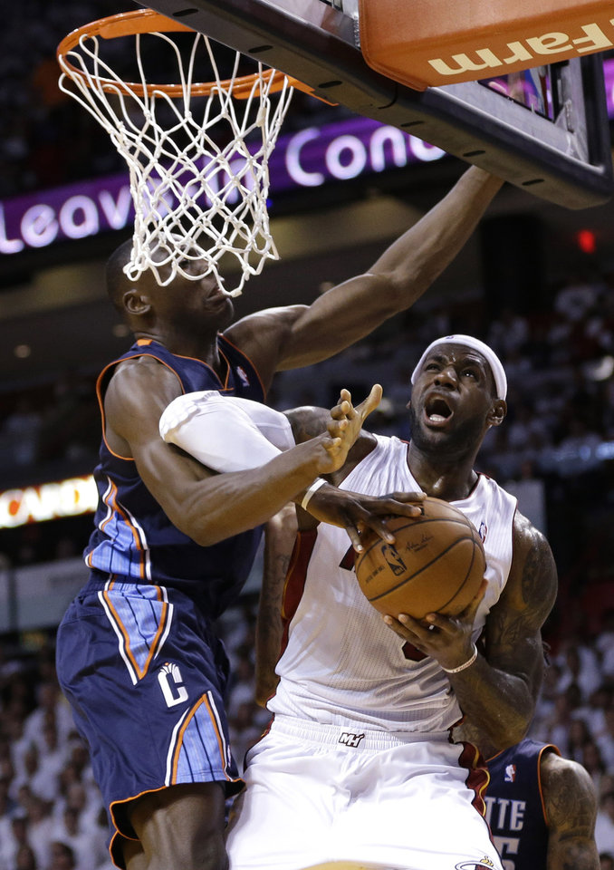Photo - Miami Heat's LeBron James, right, is fouled by Charlotte Bobcats' Bismack Biyombo, left, during the first half in Game 1 of an opening-round NBA basketball playoff series, Sunday, April 20, 2014, in Miami. (AP Photo/Lynne Sladky)