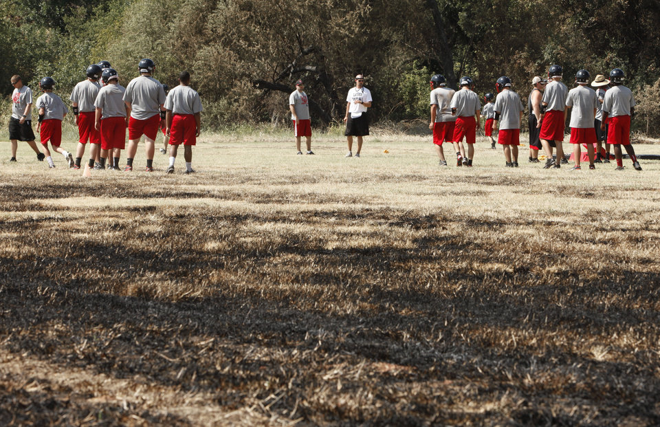 Photo - WILDFIRE / AFTERMATH / DAMAGE: Luther High School football players work out on the practice field which was partially burned by recent wildfires in Luther, OK, Tuesday, August 7, 2012,  By Paul Hellstern, The Oklahoman