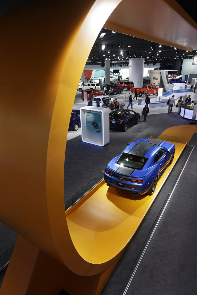 The Hot Wheels edition of the Chevrolet Camaro sits on an oversized track that appears to swoop down from the ceiling at the North American International Auto Show in Detroit, Tuesday, Jan. 15, 2013. General Motors Co. last year announced it would sell the vehicle with Hot Wheels logos and other toy-inspired touches such as red-lined wheels. (AP Photo/Carlos Osorio)