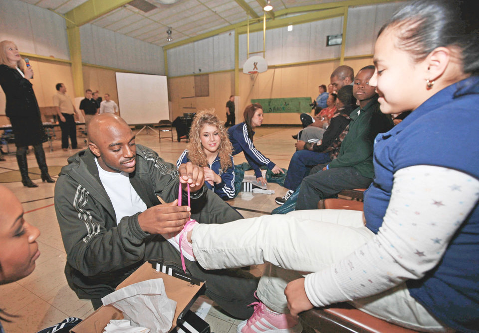 Thunder guard Damien Wilkins puts a new pair of adidas tennis shoes on the feet of a student at Dunbar Elementary on Monday. Photo provided