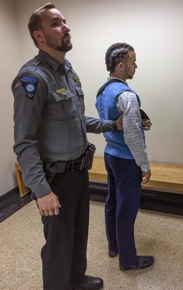 Photo -  Gerron Cobb is taken into custody by a Cleveland County Sheriff´s deputy Wednesday after after a judge said he violated a court order. Cobb, 22, was shot twice during an altercation at Penn Square Mall on Dec. 19. [TIM WILLERT/THE OKLAHOMAN]