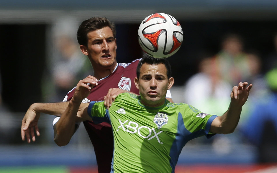 Photo - Seattle Sounders' Marco Pappa, right, and Colorado Rapids' Thomas Piermayr, left, battle for a header, Saturday, April 26, 2014, in the first half of an MLS soccer match in Seattle. (AP Photo/Ted S. Warren)