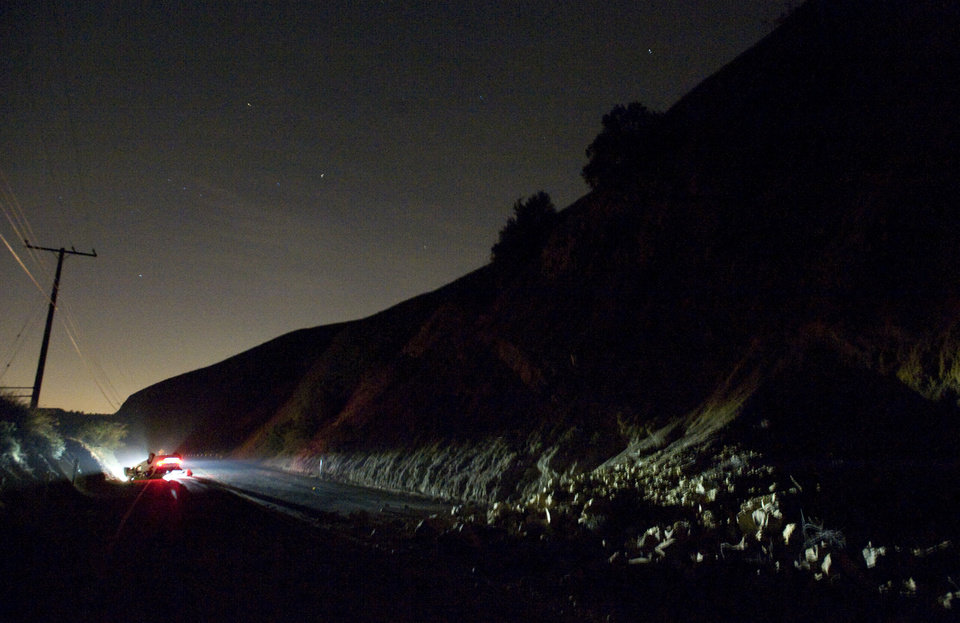 Photo - A car sits rolled over near a rockslide, right, in the wake of Friday nights March 28, 2014 earthquake on Carbon Canyon Road in Brea, Calif., near Olinda Village. (AP Photo/The Orange County Register, Rod Veal)