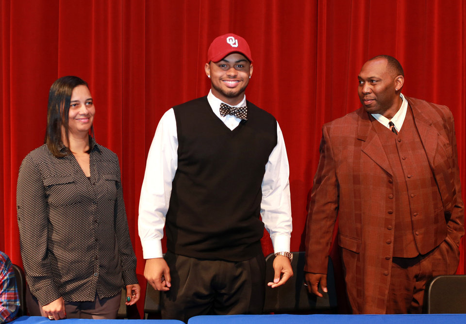 Photo - Atlee linebacker Ricky DeBerry wears Oklahoma cap with his parents, Angela and Rick DeBerry after he announced Friday morning that he will play for Oklahoma at Atlee High School in Mechanicsville on December 19, 2014. [COURTESY RICHMOND TIMES DISPATCH]