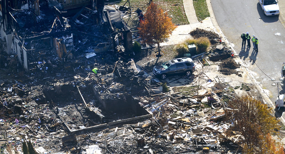 Photo -   Citizens Energy workers continue their investigation Monday afternoon Nov. 12, 2012 by digging into the front sidewalk looking for possible explanation into the explosion in Indianapolis. They are checking gas line, but caution it is too soon to rule other possible causes, (AP Photo/ WTHR Chopper 13 /The Indianapolis Star, Matt Kryger) NO SALES